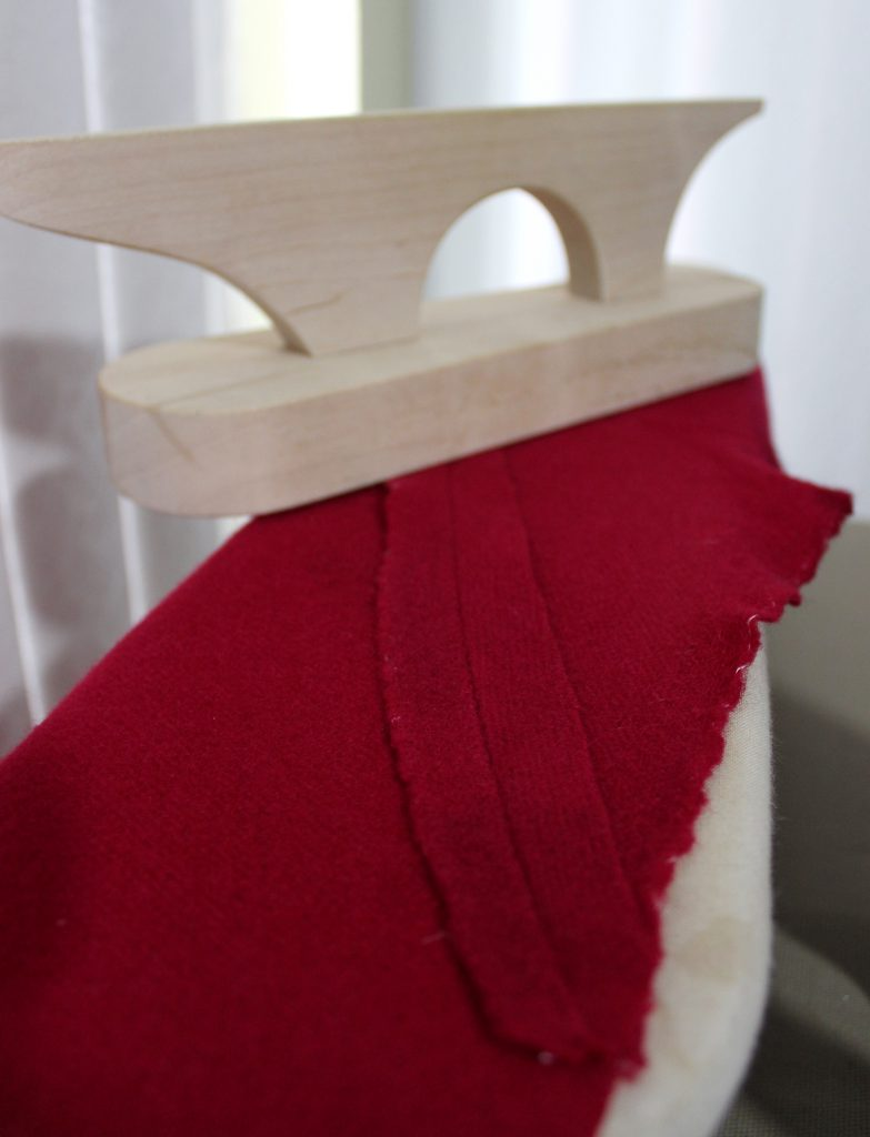 Flattening the petticoat skirt seams with a wooden clapper