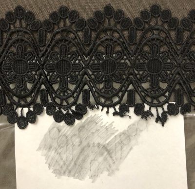 Black lace and white paper rubbing